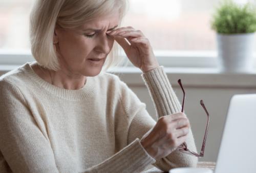 Mujer frente a un ordenador mostrando síntomas de fatiga visual