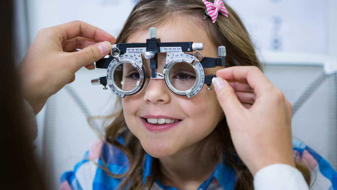female optometrist examining young patient with trial frame 1 1 1